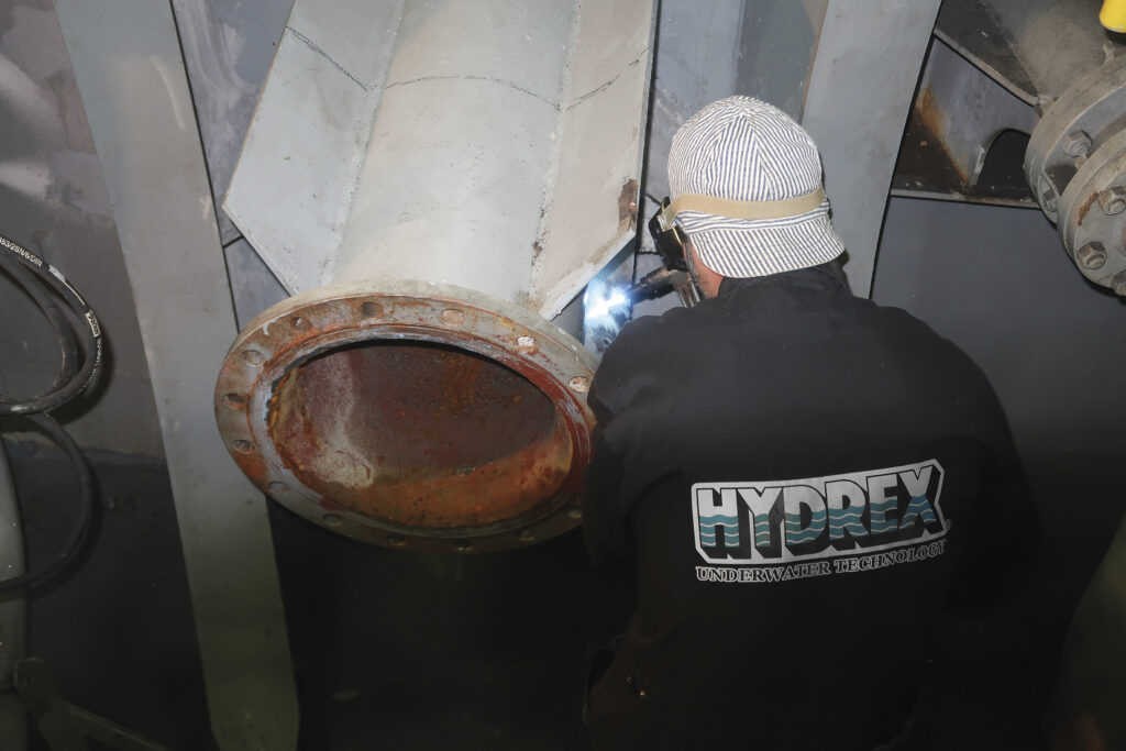 Hydrex technician cutting away the old pipe